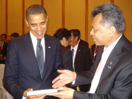 "At the ASEAN-US Leaders Meeting, Surin Pitsuwan, Secretary-General of ASEAN, presented a copy of ""Realizing the ASEAN Economic Community"" to President Barack Obama."